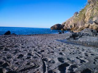 Arena negra, mar azul