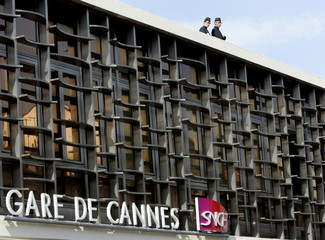 Police officers watch crowds of fans from the roof of the Cannes train station after the arrival of ..