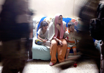 FAMILY WATCHES IRAQI CIVIL DEFENCE RECRUITS RAID APARTMENT IN BAGHDAD.
