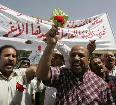 Iraqi workers chant slogans while holding plastic flowers during May Day celebration in Baghdad