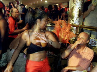 REVELER DANCES FOR A TOURIST AT RED AND BLACK CARNIVAL GALA IN RIO.