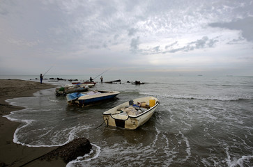 Fishermen fish on a beach in the city of Durres