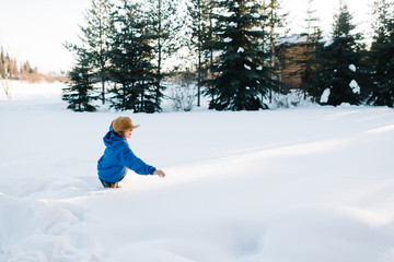 Boy playing in snow in winter