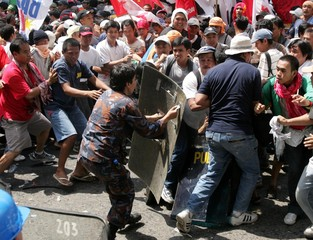 Anti-riot policewoman uses her shield to push back protesters as demonstrators march near the presidential palace in Manila