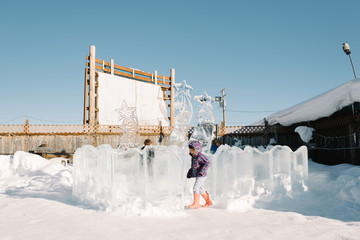 Children playing outdoors in winter ice sculpture