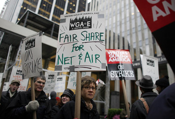 Members of the Writers Guild of America walk the picket line in front of the News Corporation building as they strike for better wages in New York