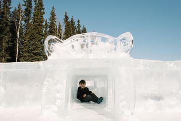 Boy sitting in ice sculpture