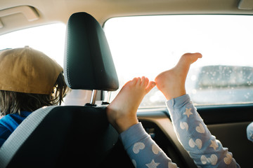 Barefoot child riding in car