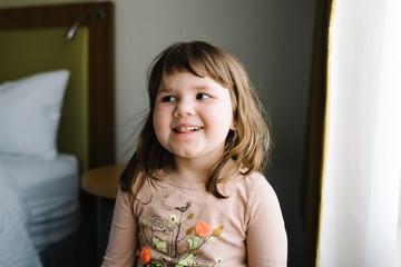Little girl smiling in bedroom