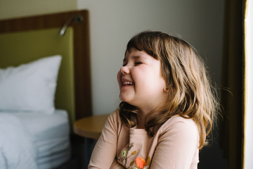Little girl laughing in bedroom
