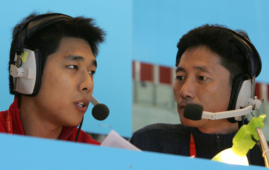 Retired South Korean short track speed skater Kim Dong-sung (L) gives a commentary beside sport repo..