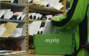 A courier of German postal firm PIN Group sorts letters at a Pin office in Essen