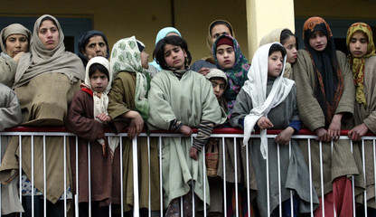 Kashmiri women watch the funeral procession of a political worker in Srinagar.