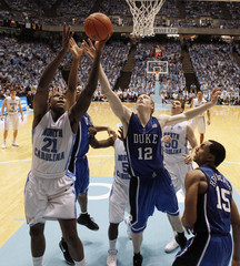 The University of North Carolina's Deon Thompson battles Duke University's Kyle Singler for a rebound during their NCAA basketball game in Chapel Hill