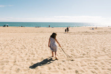 Girl playing with stick on beach