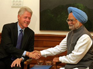 Former U.S. President Clinton shakes hands with Indian Prime Minister Manmohan during their meeting ...