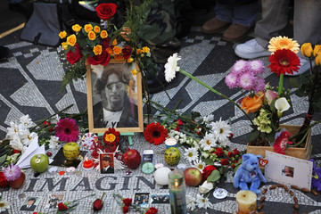 """Candles, flowers and pictures adorn the """"Imagine"""" memorial mosaic at Strawberry Fields in Central Park in New York"""