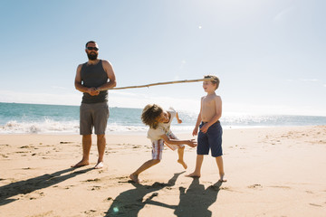 Father playing with children on beach
