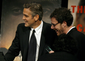 Writer Ethan Coen laughs as he accepts the award for Best Adapted Screenplay from actor George Clooney in New York