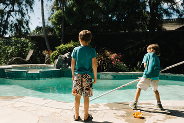 Two boys cleaning swimming pool