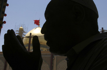 A Shi'ite worshipper is silhouetted as he prays during Friday prayers at the Imam Hussein shrine in the holy city of Kerbala