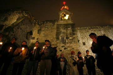 Palestinians hold candles in front of Church of Nativity in Bethlehem