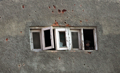 An Indian soldier looks from the bullet riddled window of a hotel during a shootout in Srinagar