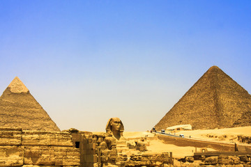 Close up of the face of the Great Sphinx with a set of pyramids in the background on a beautiful clear blue sky day in Giza, Cairo, Egypt