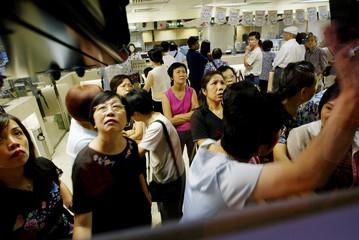 SMALL INVESTORS MONITOR SHARE PRICES INSIDE BANK IN HONG KONG.