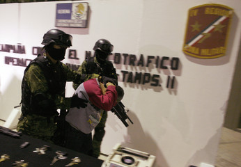 Soldiers escort drug hitman Carlos Adrian Martinez, 32, as he is presented to the media at the military zone on the outskirts of Monterrey