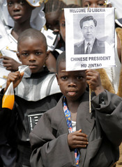 A child holds a poster of Chinas President Hu on Hu's arrival in Monrovia