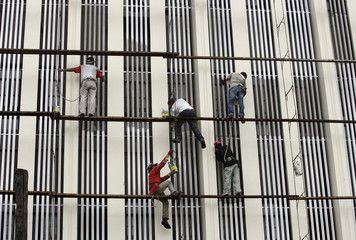 Labourers repaint an old building in Manila's Makati financial district