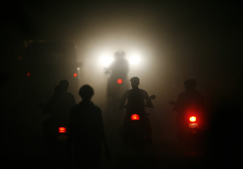 Motorcyclists ride through a haze on a road in the industrial town of Vapi