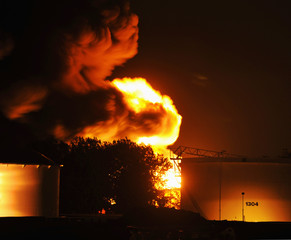 Flames illuminate the night after lightning from a violent storm ignited a gasoline storage tank at a petroleum distribution terminal in Kansas City