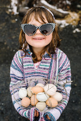 Girl wearing sunglasses and holding basket of eggs
