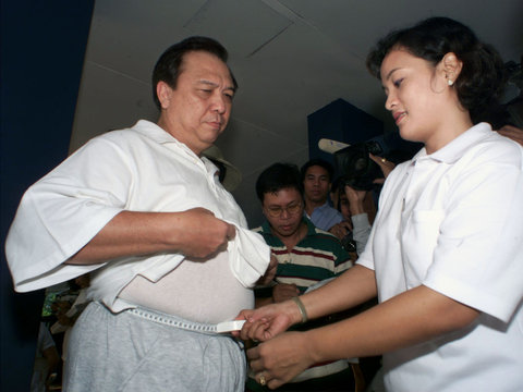 PHILIPPINE NATIONAL POLICE GENERAL ROMULO SALES WAIST IS MEASURED BY A POLICEWOMAN.