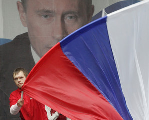 Supporters of Russian President Vladimir Putin wave a state flag with Putin's portrait in the background as they celebrate his 55th birthday in central Moscow