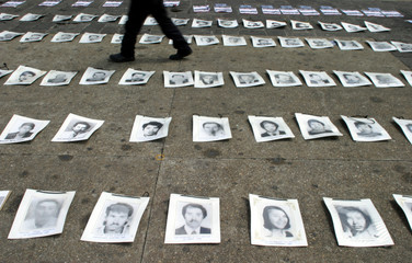 A man walks past pictures of people missing and presumed dead in Guatemala City