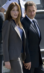 France's President Nicolas Sarkozy and his wife Carla Bruni-Sarkozy walk on the tarmac of the Villacoublay military airport