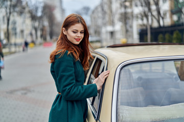a woman in a green coat leaned against the car