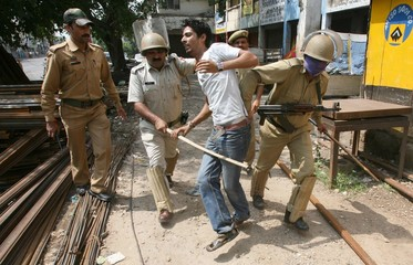 Policemen beat a demonstrator during a protest in Jammu