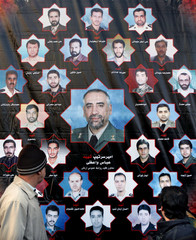 Iranian men look at banner with pictures of Iranian army members who were killed in plane crash in Tehran