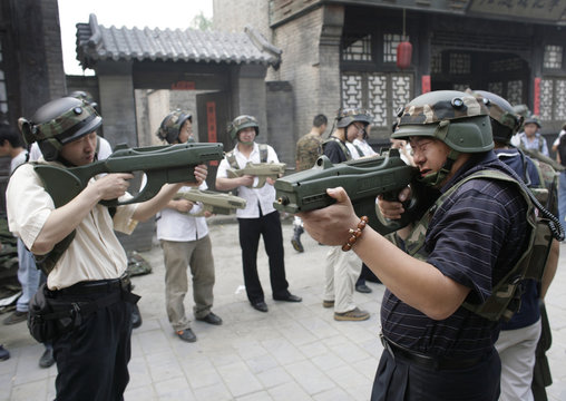 """Customers of Xuelang Outdoor Sports Club use laser guns during a """"Counter-Strike"""" game in Beijing"""