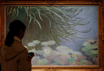A woman walks through exhibition featuring rarely seen works by Claude Monet in New York