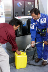 ECUADOREAN PEDESTRIAN BUYS FUEL IN A PLASTIC TANK.