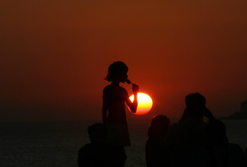 A girl eats ice cream in the backdrop of the setting sun at a seafront in Mumbai