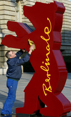 A worker cleans a huge mock-up of the Berlin bear award advertising the upcoming 55th International ..