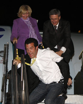 Conservative leader and Canada's PM Harper reaches for comedian Rick Mercer as he jokingly falls down the stairs to Harper's campaign plane in Toronto