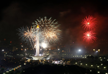 Fireworks explode from the National Monument during New Year celebrations in Jakarta