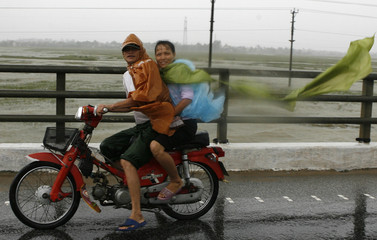 Residents ride a motorcycle in the rain in Vietnam's central Ha Tinh province